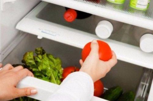 женщина кладет томат в холодильник