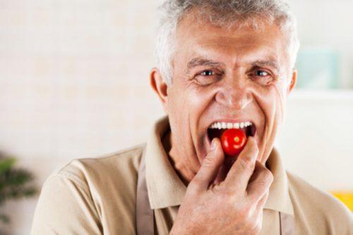 мужчина кушает помидоры